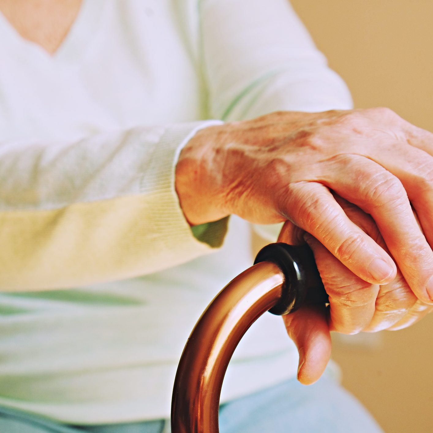 Elderly woman in nursing home, wrinkled hand with clearly visible veins holding walking quad cane. Old age senior lady arms with freckles lay on aid stick handle bar. Background, close up, copy space.